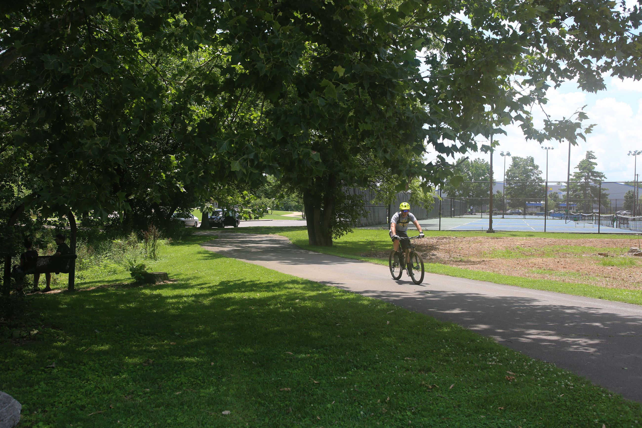 Bicyclist riding on path in dappled shade, trees, tilled area, and tennis courts in background