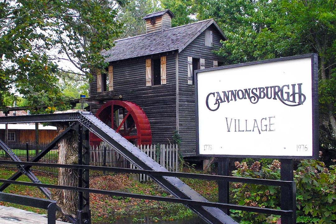 Wooden grist mill building with red waterwheel among trees, behind Cannonsburgh Village sign. Summer
