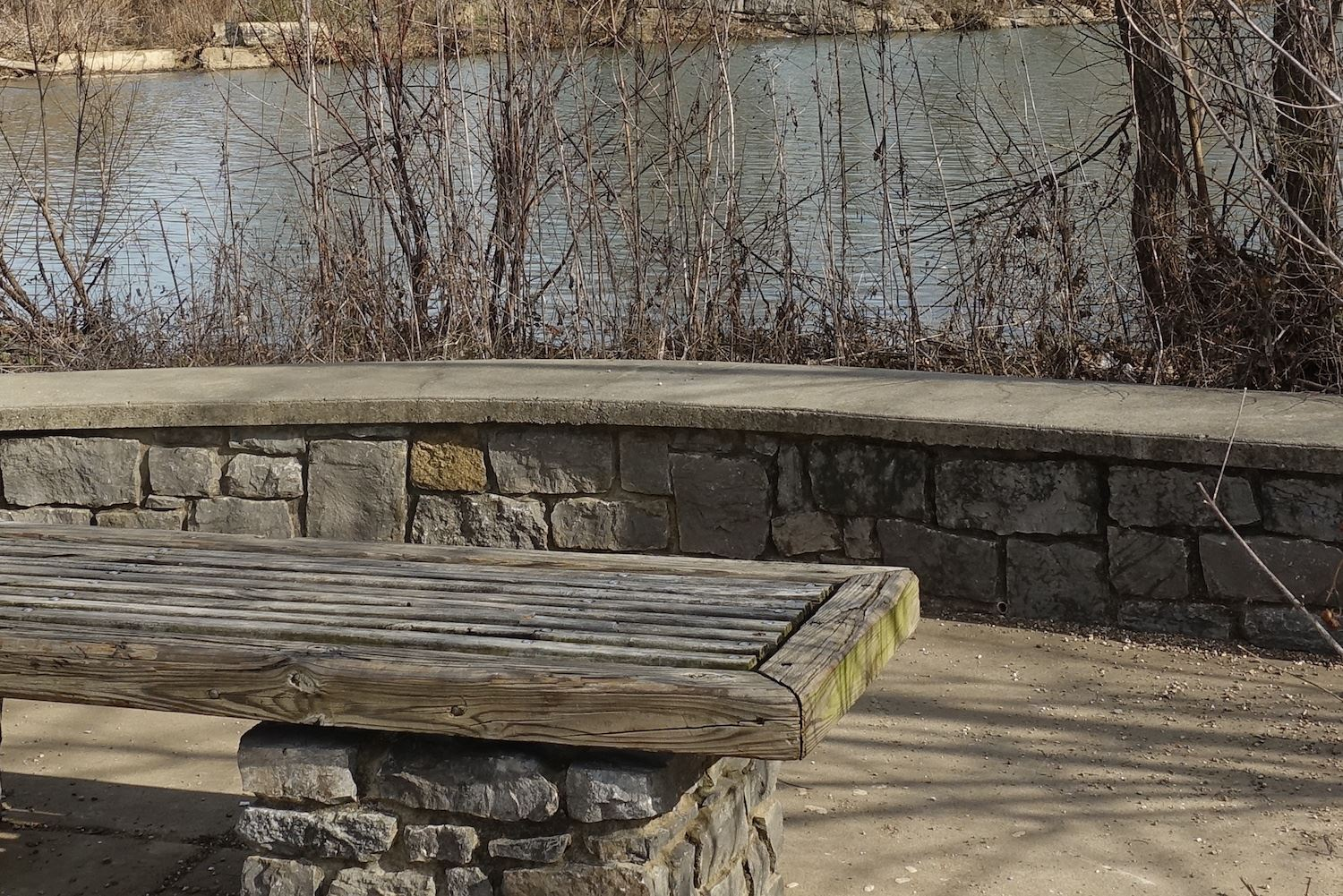 Stone and wood bench in front of low stone wall with river in background