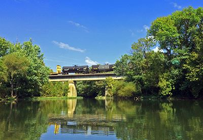 Train crossing a bridge over a river, against blue sky, and reflected in the water