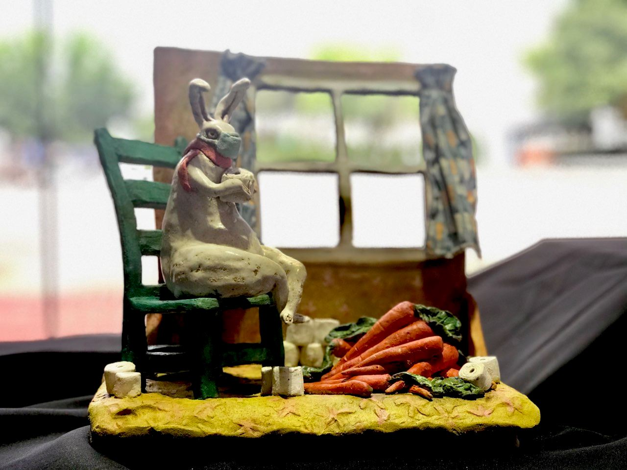 Sculpture of bunny in room with carrots and toilet paper