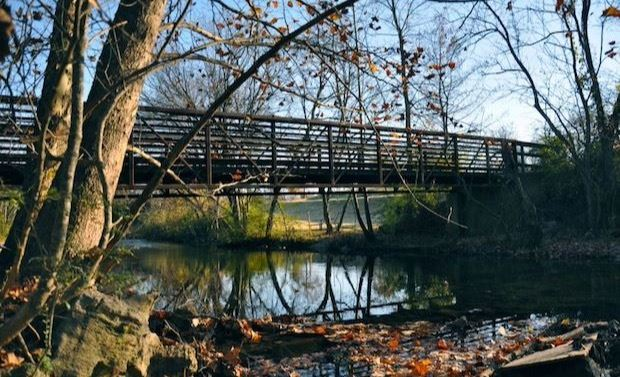 Pedestrian bridge over creek in autumn: Sycamore and other trees, fallen leaves, water, sky, rocks