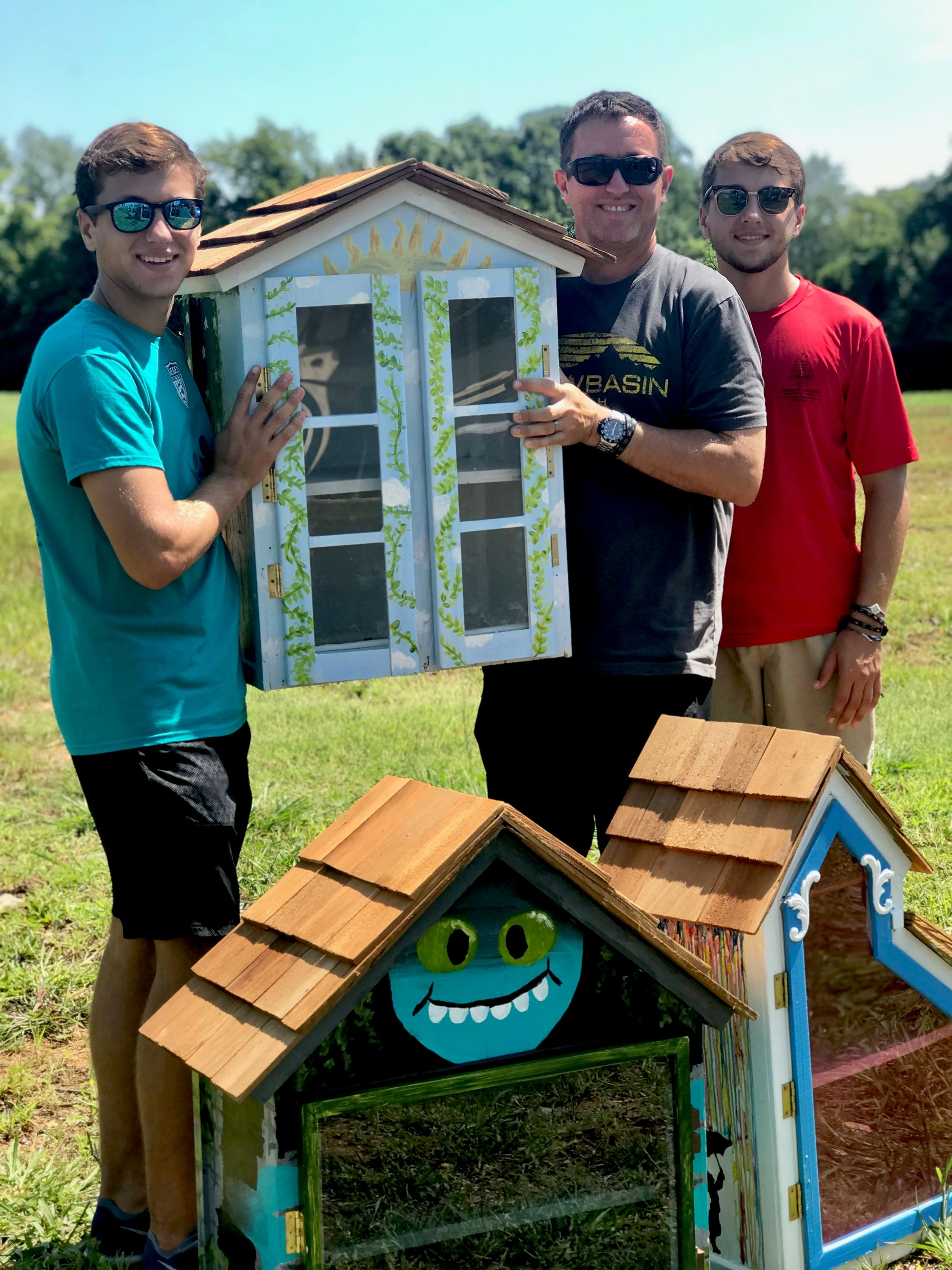 Local Eagle Scout poses with finished Little Libraries with father and brother prior to installation